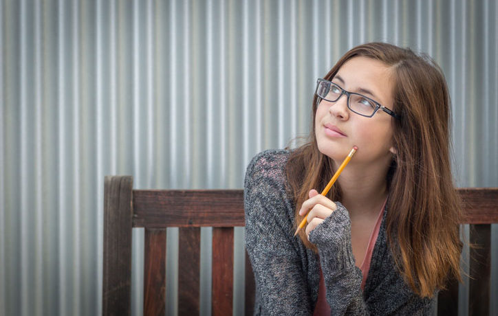 Pretty Young Daydreaming Female Student With Pencil Sitting on Bench Looking to the Side.