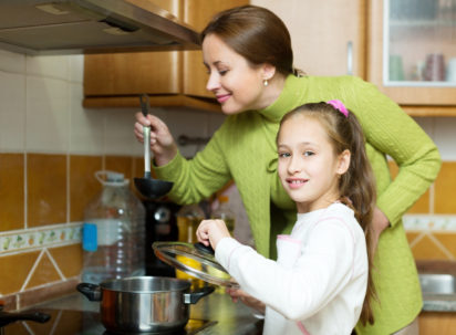 child with her adult mother prepare the soup by the stove in his kitchen. Focus on the child